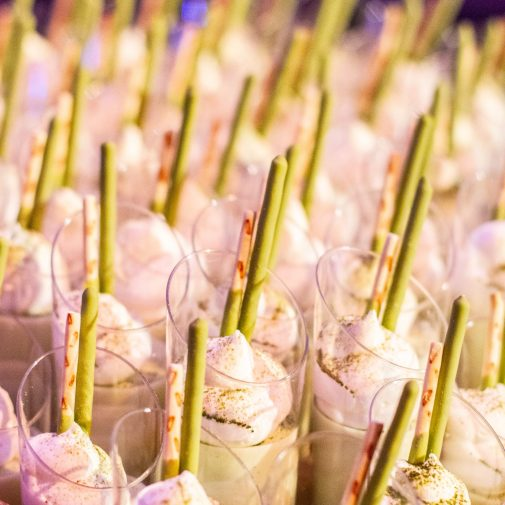 Matchas desserts in small clear glasses topped with wipped cream and Pocky Sticks are lined up.