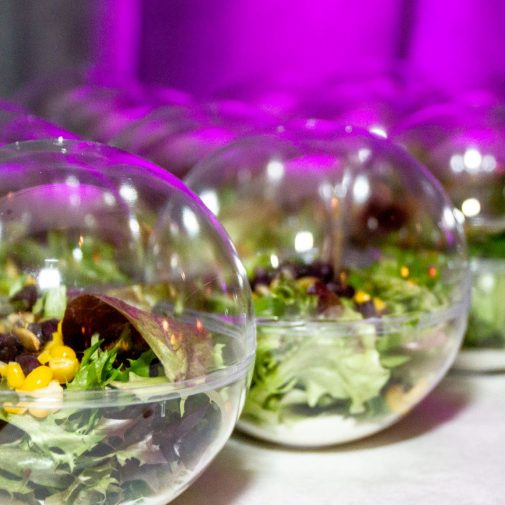 Salads inside of round glass orbs are lined on a table.